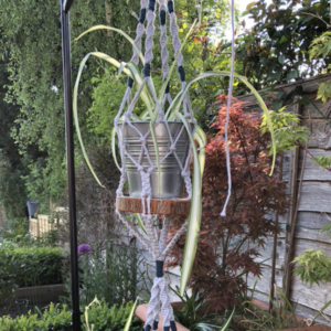 Macrame Pot Holder - Isabella - This lovely versatile hanging pot holder allows you to have two pots hanging in the one space. Perfect for using a small space for maximum impact. Isabella is a Light Grey with Peacock Blue highlights and has two small wooden shelves to hold your pots in place. Maybe use the bottom one for your utensils in your kitchen or even as a storage pot for your office. Made from 100% recycled cotton. Approx 132cm long. Colours may vary due to your screen settings and photography. Each one is unique Approx 1m long. Colours may vary due to your screen settings and photography. Pots and plants not included.